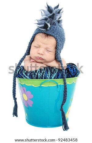 Newborn baby sleeping in a basket on white background