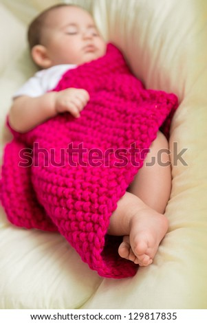 Newborn baby sleeping in bed covered with knitted blanket
