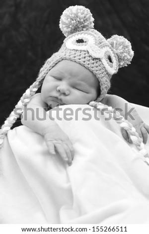 Newborn baby sleeping in the blanket wearing a hat