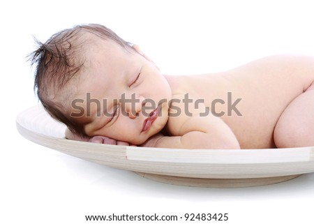 Newborn baby sleeping in wood bowl on white background