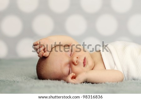 Newborn baby sleeping on blue blanket. Soft focus, very shallow DOF.