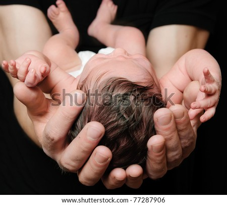 Newborn baby Sleeping on farther Arms on Black Background