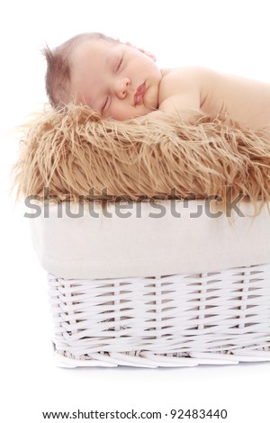 Newborn baby sleeping on fur in a basket on white background