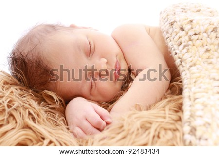 Newborn baby sleeping on soft fur under a knit blanket