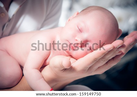 Newborn baby sleeping on the shoulder of his father
