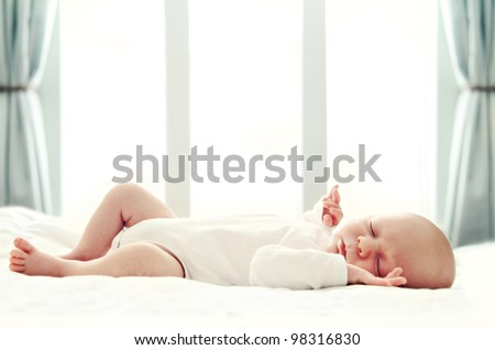 Newborn baby sleeping on white blanket in front of a window. Soft focus, very shallow DOF. - stock photo