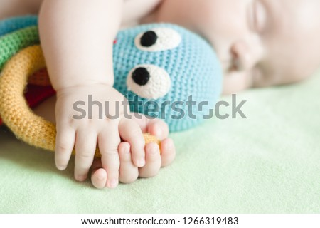 Newborn baby sleeps with color octopus toy, knitted from yarn. Toys for infants