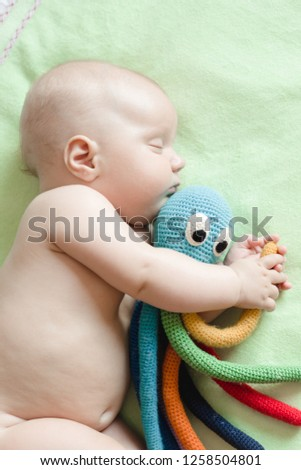 Newborn baby sleeps with color octopus toy, knitted from yarn. Toys for premature infants