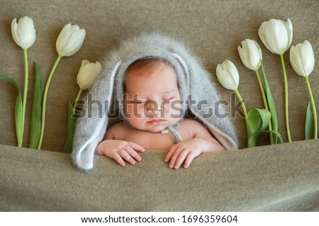 Newborn baby wearing a rabbit hat with ears.Spring.Spring composition.Photoshoot of newborns.Beautiful girl with flowers. Newborn baby with tulips. Mothers Day.March 8.Easter bunny.Easter postcard.