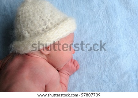 Newborn baby with cap is sleeping on blue blanket.