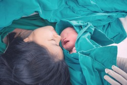 Newborn baby with mother and father in hospital. Newborn child seconds and minutes after birth.