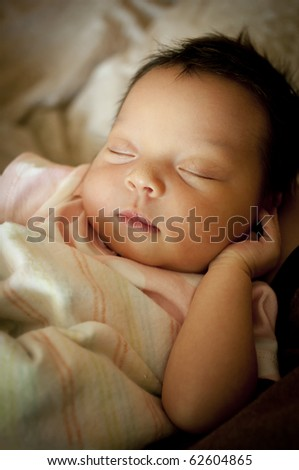 Newborn baby wrapped in blanket sleeping on her back.