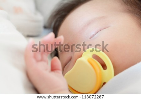 Newborn beautiful baby sleeping with pacifier. Closeup portrait