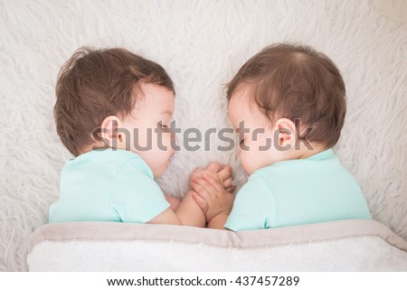 Newborn beautiful baby twins sleeping with pacifier. Closeup portrait, caucasian child