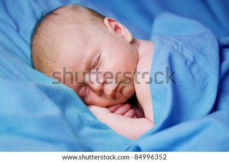 stock photo : newborn boy sleeping under blue sheet