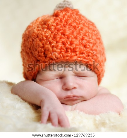 newborn boy wearing pumpkin hat