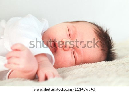 Newborn dark hair baby dressed in white is sleeping on the downy blanket close-up