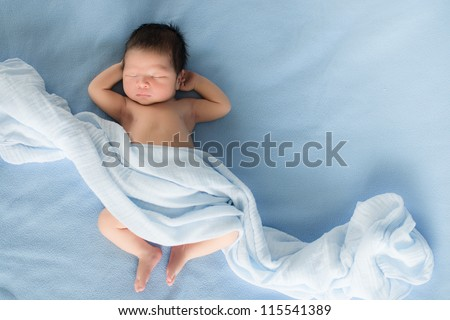 Newborn 4 day old baby boy lying on his back relaxing under a blue wrap cloth