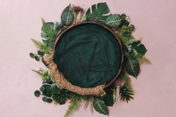 Newborn digital background - wooden bowl with pink faux fur on jute layer and pink backdrop and green leaves wreath. Tropical monstera plant wreath