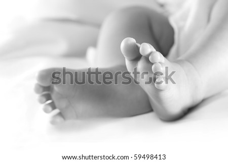 Newborn feet in black and white. Focus on right foot.