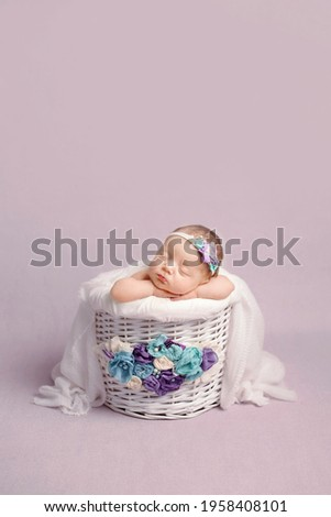 Newborn girl on a violet background. Photoshoot for the newborn.  A portrait of a beautiful newborn baby girl