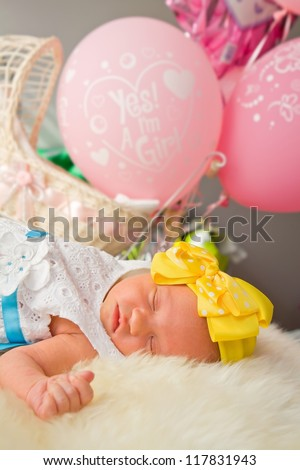 Newborn girl sleeping by pink balloons