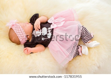 Newborn girl sleeping in cute dress