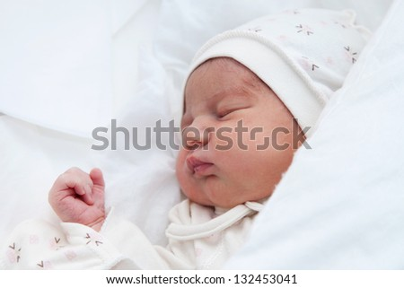 Newborn girl sleeping in her bed in the maternity hospital