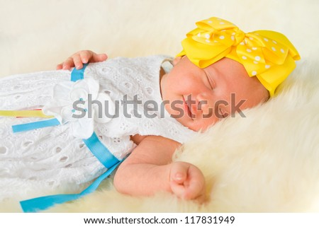 Newborn girl sleeping on fluffy carpet