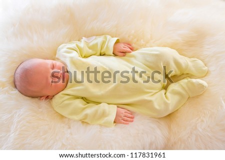 Newborn girl sleeping on fluffy carpet