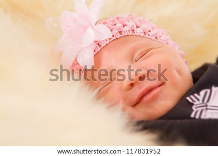 Newborn girl sleeping on fluffy carpet close-up