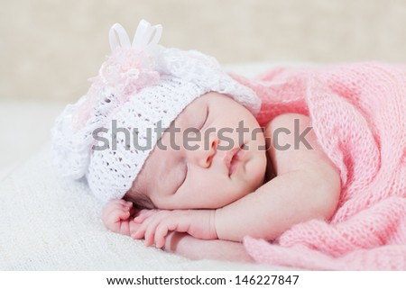 newborn girl sleeps under a knitted pink cape - stock photo