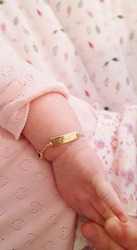 newborn hand with name bracelet