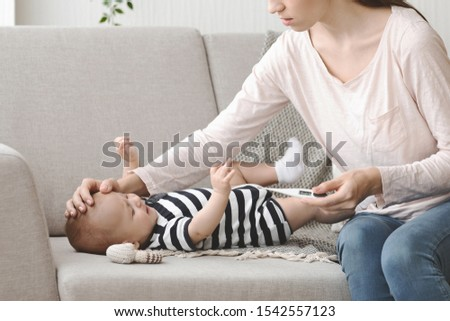 Newborn Illness. Worried mom holding thermometer and touching forehead of her ill baby, checking his temperature.