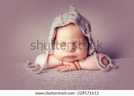 Newborn in hat on the blankets folded handles