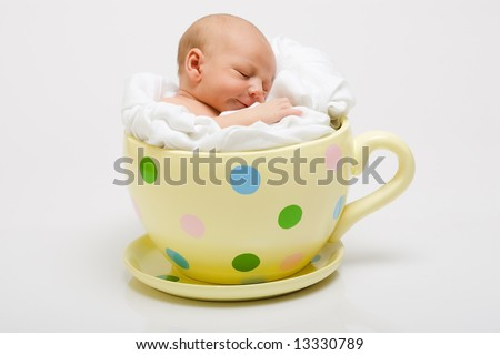 Newborn in yellow spotted cup - stock photo