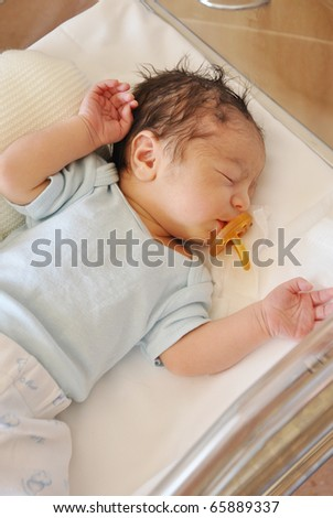 Newborn Infant Baby Boy With Pacifier in Hospital Acrylic Bassinet