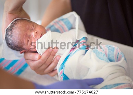 Newborn infant baby getting his first bath in the hospital. Cute little boy is bundled up and receiving a sponge bath by a nurse in his hospital room Foto stock ©