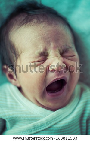 Newborn peacefully sleeping, picture of a baby curled up sleeping on a blanket
