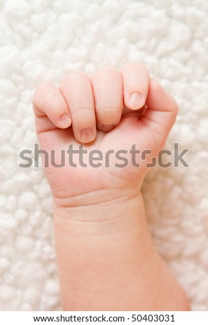 newborn's baby hand in a fist on a blanket