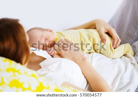 Newborn sleeping child in the hands of mother. Co-sleeping mother and baby child. Young beautiful mother recovering after childbirth.
