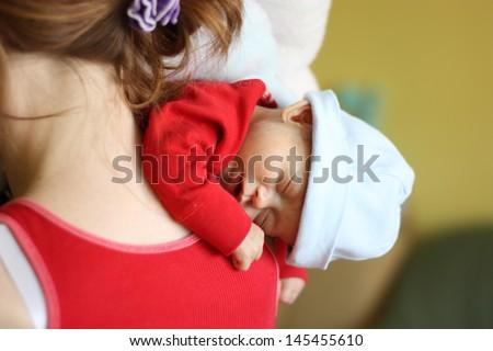 Newborn sleeping on mother's shoulder
