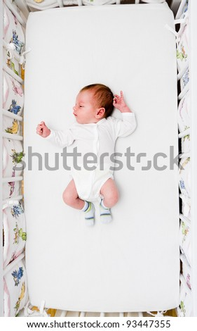 Newborn small boy sleeping in his big bed