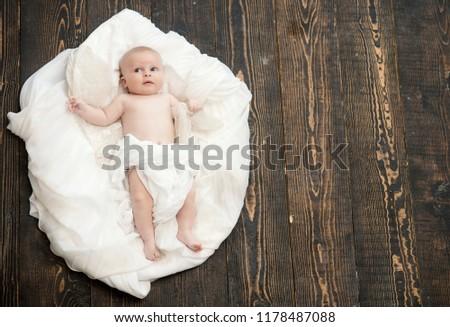 Newborn toddler with blue eyes and curious face on wooden background. Infant covered with white blanket. Baby lying on white soft duvet designed as cloud or nest. Childhood and innocence concept #1178487088