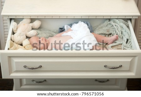 Newborn toddler with blue eyes and serious face surrounded by soft knitted blankets. Baby lies in white wooden chest drawer. Infant covered with white duvet near toys. Childhood and innocence concept #796571056