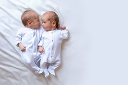 Newborn twins on the bed, in the arms of their parents, on a white background. Life style, emotions of kids. Multiple pregnancy. The large family
