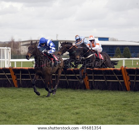 NEWBURY, BERKS- MAR 27: Jockey Aidan Coleman (blue and white) takes lively fling over hurdles in the first race at Newbury Racecourse, UK, March 27, 2010 in Newbury, Berks