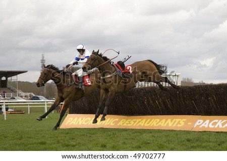 NEWBURY, BERKS - MAR 27: Jockey warren marsden takes wychwoods legend over fences next to a loose horse (over sixty)  in the second race at Newbury Racecourse, UK, March 27, 2010 in Newbury, Berks