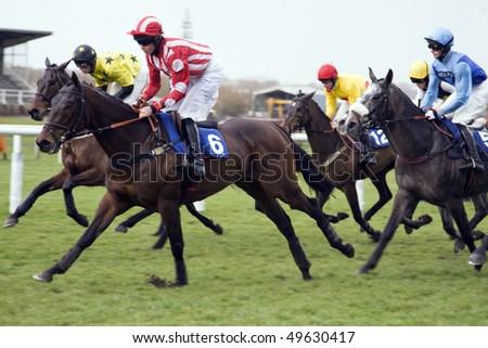 NEWBURY, BERKS- 26 MAR:  Jockeys jostle for position over hurdles in the fifth race at Newbury Racecourse, Newbury, Berks on 26 March 2010