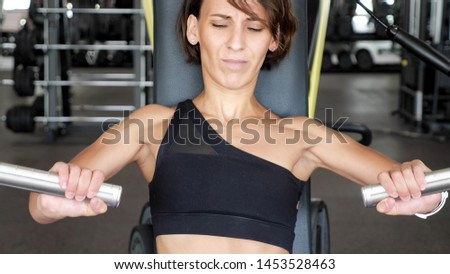Newcomer woman in gym is making exercises for arm muscles on a fitness-station pushing with efforts. Sports workout first time. Fitness and bodybuilding concept.